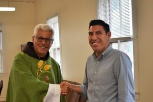 Fr. Vince Mesi, OFM, pastor of Mission San Luis Rey Parish, congratulates Angel Ibarra at the Social Outreach & Justice open house.
